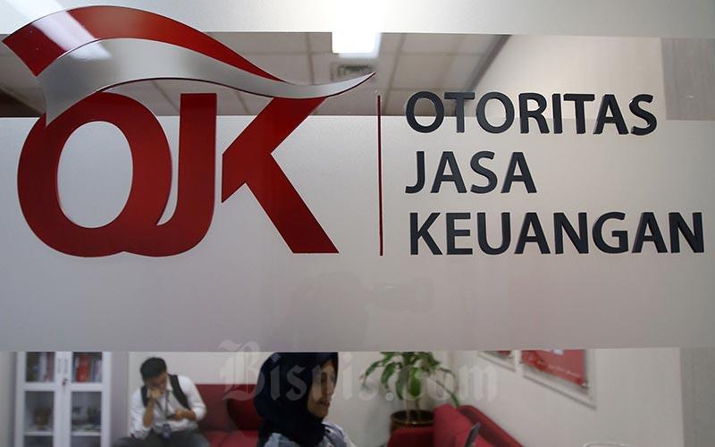 Karyawan berada di dekat logo Otoritas Jasa Keuangan. - Bisnis/Abdullah Azzam