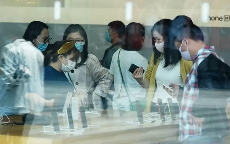 Warga memakai masker pelindung menyusul penyebaran penyakit  Covid-19 di Apple Store saat penjualan iPhone SE baru dimulai, di Hangzhou, Provinsi Zhejiang, China, Jumat (24/4/2020). - Antara