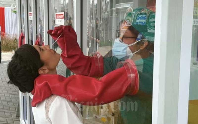 Petugas melakukan tes usap atau PCR test virus Covid-19 di Genomik Solidaritas Indonesia (GSI), Jakarta, Rabu (12/8/2020). GSI Lab melakukan tes usap Covid-19 secara walk thru, ride thru, dan drive thru. Bisnis - Hendri T Asworo