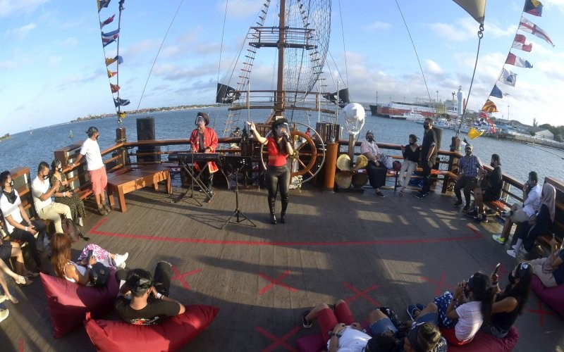 Seniman menghibur wisatawan di atas kapal Sea Safari Cruise 9 yang berlayar di perairan Benoa, Bali. - Antara/Fikri Yusuf