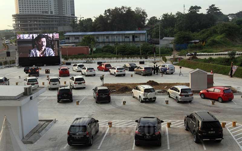 Pengunjung menyaksikan film dari dalam kendaraan (drive in) di lahan parkir Distric 1 Meikarta, Bekasi, Jawa Barat, Kamis (4/6/2020). Hiburan yang diadakan jelang kenormalan baru ini tersedia dengan kapasitas maksimal 30 unit mobil dan tanpa dipungut bayaran. - Bisnis/Arief Hermawan P.