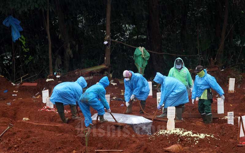Petugas pemakaman menurunkan peti jenazah pasien Covid-19 di TPU Pondok Ranggon, Jakarta, Kamis (9/4/2020). Bisnis - Arief Hermawan P