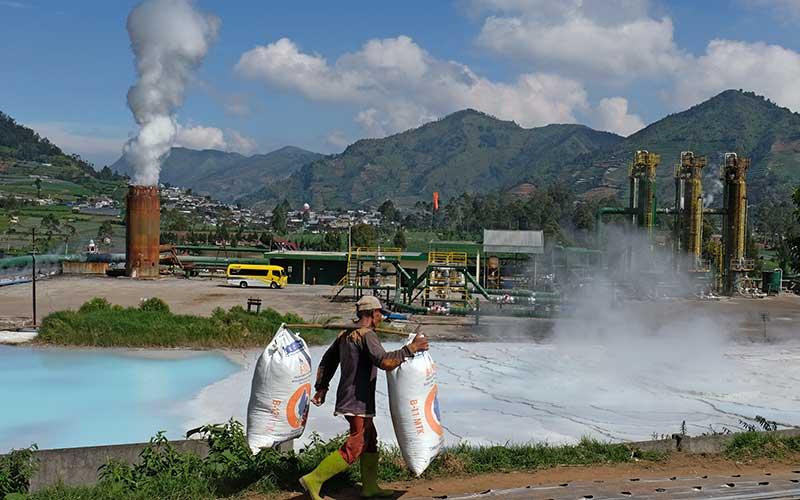 Seorang warga memikul pupuk kandang di perladangan sekitar instalasi sumur Geothermal atau panas bumi PT Geo Dipa Energi di kawasan dataran tinggi Dieng Desa Kepakisan, Batur, Banjarnegara, Jawa Tengah, Rabu (19/8/2020). ANTARA FOTO - Anis Efizudin