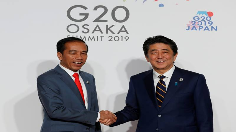 Presiden Indonesia Joko Widodo disambut oleh Perdana Menteri Jepang Shinzo Abe pada saat kedatangannya untuk sesi foto sambutan dan keluarga di KTT para pemimpin G20 di Osaka Jepang, 28 Juni 2019. - Reuters