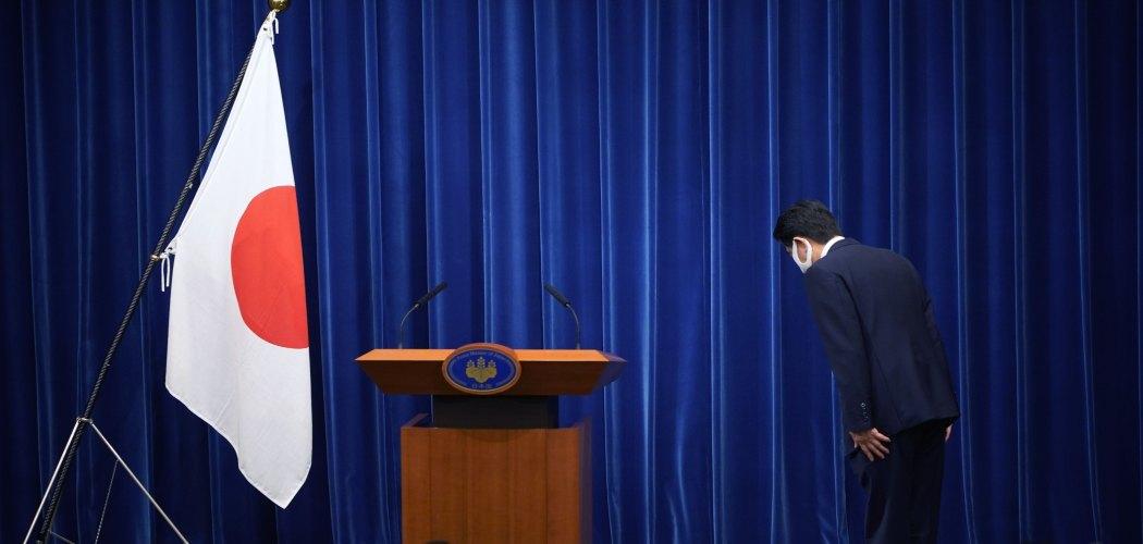 Shinzo Abe membungkukkan diri menghormati bendera Jepang usai mengumumkan pengunduran dirinya sebagai Perdana Menteri Jepang.  - Bloomberg