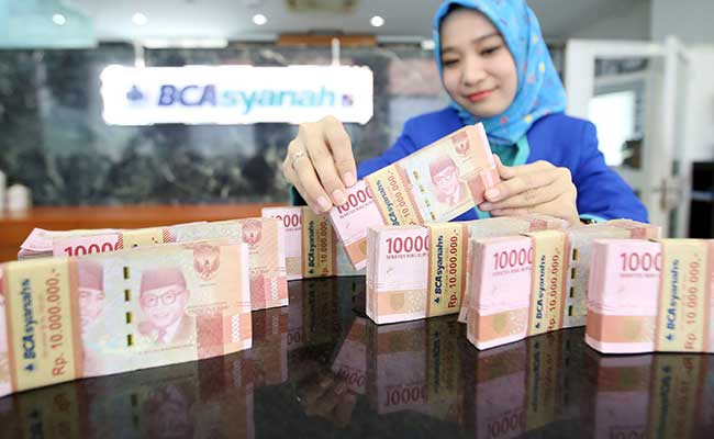 Karyawan menata uang Rupiah di cabang Bank BCA Syariah di Jakarta. Bisnis - Abdullah Azzam