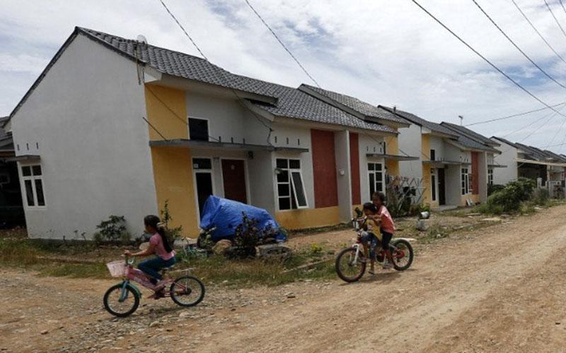 Anak-anak bersepeda melintas di depan rumah kompleks perumahan bersubsidi di Desa Lam Ujong, Kecamatan Baitussalam, Aceh Besar, Aceh./Antara - Irwansyah Putra