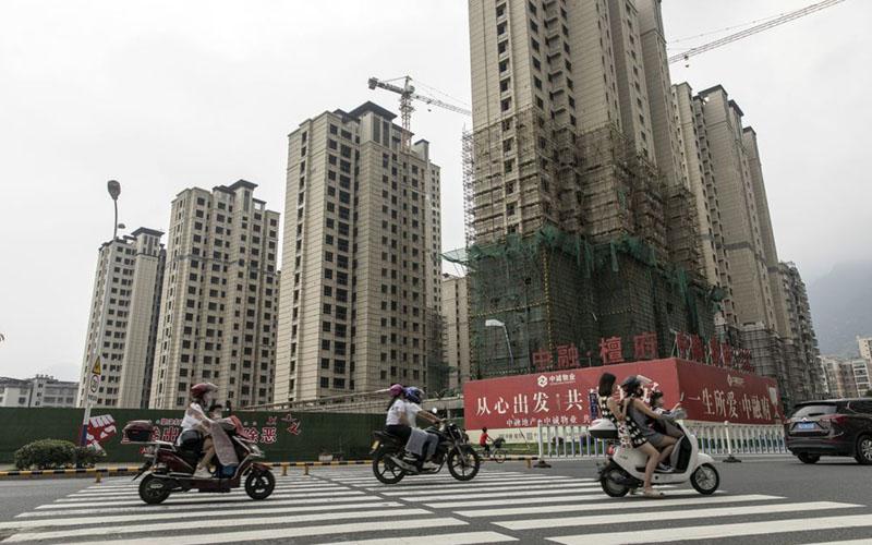 Pengendara motor melintasi jalan di dekat bangunan hunian yang sedang dibangun di Ningde, Provinsi Fujian, China./Bloomberg - Qilai Shen