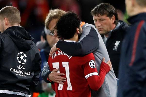 Pelatih Liverpool Jurgen Klopp memeluk striker Mohamed Salah. - Reuters
