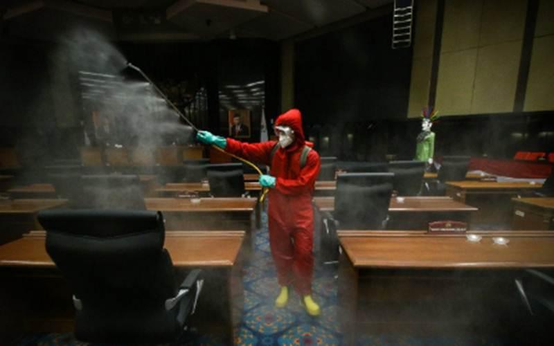 Petugas menyemprotkan cairan disinfektan di ruang sidang paripurna DPRD DKI Jakarta, Rabu (29/7/2020). - ANTARA/Rivan Awal Lingga\n\n