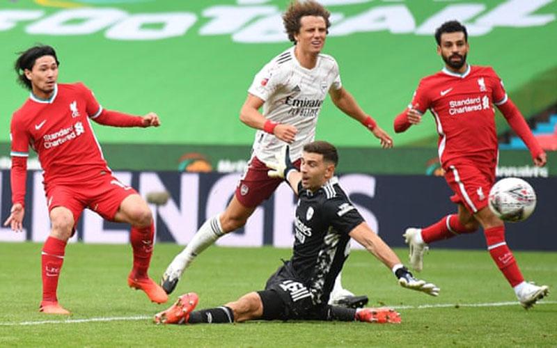 Pemain Liverpool Takumi Minamino (kiri) menjebol gawang Arsenal yang dikawal kiper Emiliano Martinez. - The Guardian