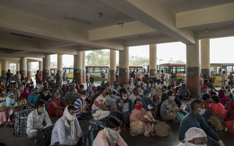Pekerja migran menunggu di terminal bus untuk pulang ke kampung halaman masing-masing, di Greater Noida, Uttar Pradesh, India, Jumat (29/5/2020). - Bloomberg/Anindito Mukherjee
