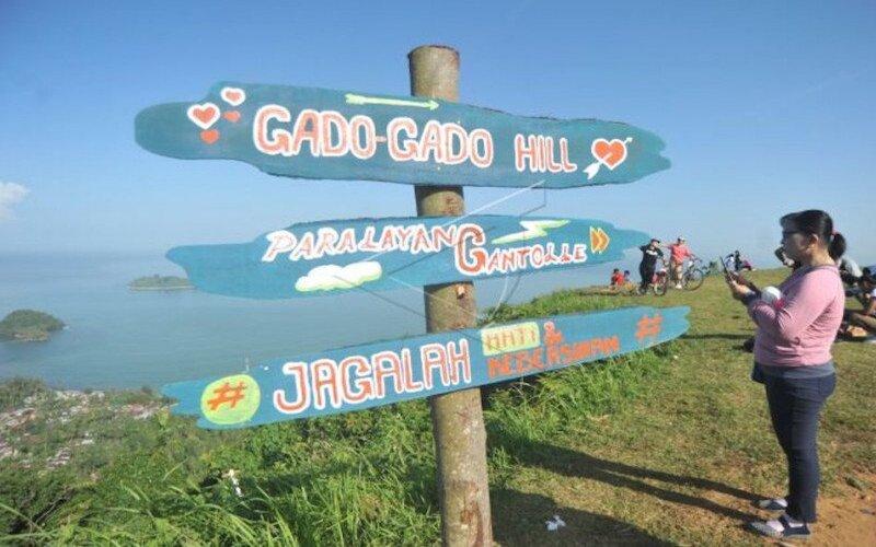 Warga menikmati panorama dari puncak Bukit Gado-gado, di Padang, Sumatra Barat, Minggu (28/6/2020). - Antara/Iggoy el Fitra