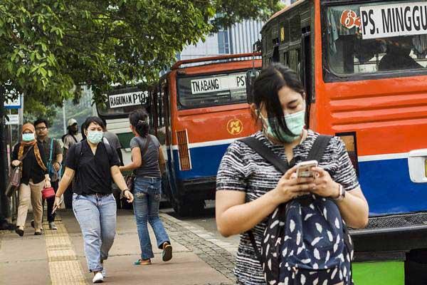 Sejumlah orang menggunakan masker untuk melindungi diri dari polusi udara saat menyeberang di jembatan penyeberangan orang di Sarinah, Jakarta, Senin (9 - 10). Berdasarkan data Indeks Standar Pencemaran Udara, kualitas udara di Jakarta kerap mencapai kondisi tidak sehat bahkan sangat tidak sehat.ANTARA/Galih Pradipta