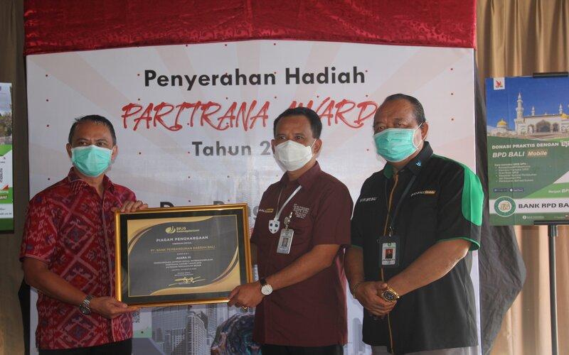Deputi Direktur BP Jamsostek Wilayah Bali, Nusa Tenggara, dan Papua Deny Yusyulian (kiri) menyerahkan penghargaan kepada Dirut BPD Bali I Nyoman Sudharman (tengah) disaksikan Komisaris Non Independen Wisnu Bawa Temaja (kanan).Bisnis - Luh Putu Sugiari