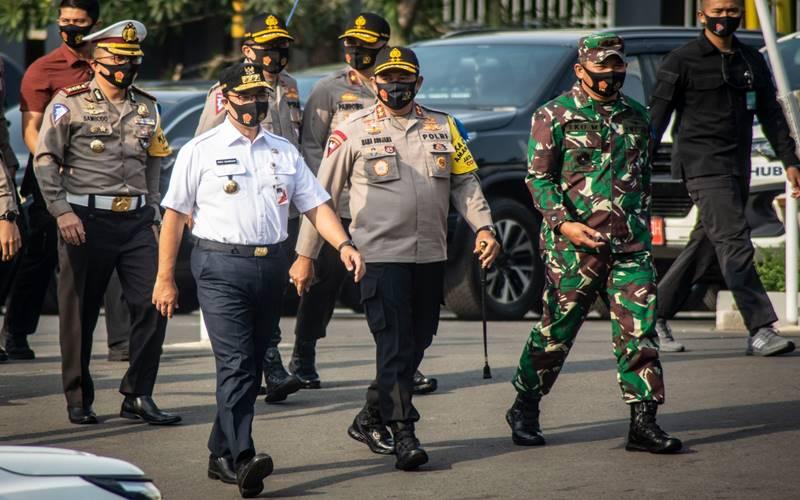 Kapolda Metro Jaya Irjen Pol Nana Sudjana (tengah), Gubernur DKI Jakarta Anies Baswedan (kedua kiri), dan Pangdam Jaya/Jayakarta Mayjen TNI Eko Margiono (kedua kanan) menghadiri Apel gelar Pasukan Operasi Patuh Jaya Tahun 2020 di Polda Metro Jaya, Jakarta, Kamis (23/7/2020). Operasi Patuh Jaya 2020 tersebut berlangsung selama 14 hari dimulai 23 Juli sampai 5 Agustus 2020 dengan mengerahkan sebanyak 1.807 personel gabungan dari unsur TNI, Polri, Satpol PP, dan Dishub DKI Jakarta. - Antara
