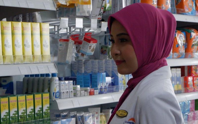 Seorang petugas di Apotik Kimia Farma sedang melihat persediaan barang yang dijual di etalase. - Kimia Farma