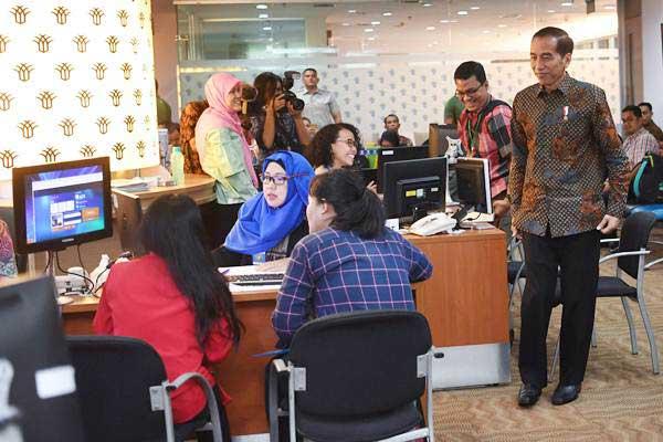 Presiden Joko Widodo (kanan) meninjau layanan konsultasi Online Single Submission (OSS) BKPM di PTSP BKPM Jakarta, Senin (14/1/2019). - ANTARA/Wahyu Putro