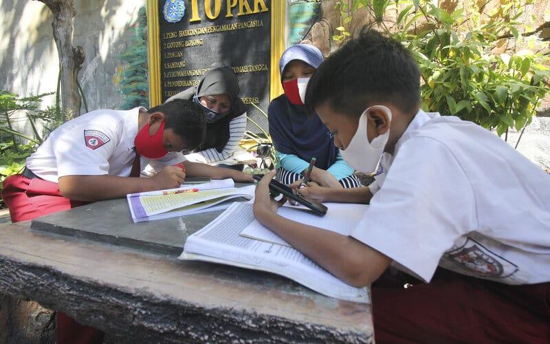 Sejumlah pelajar didampingi orang tuanya belajar secara daring di Mulyorejo Selatan Baru, Surabaya, Jawa Timur, Selasa (25/8/2020). Pengurus kampung di tempat itu menyediakan wifi gratis bagi pelajar yang terkendala biaya kuota internet untuk belajar secara daring. - Antara/Didik Suhartono