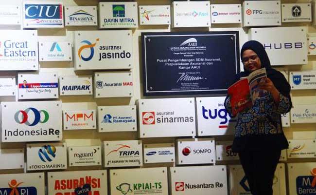 Karyawan beraktivitas di dekat logo-logo perusahaan asurasi di kantor Asosiasi Asuransi Umum Indonesia (AAUI), Jakarta, Senin (27/1/2020). Bisnis - Triawanda Tirta Aditya
