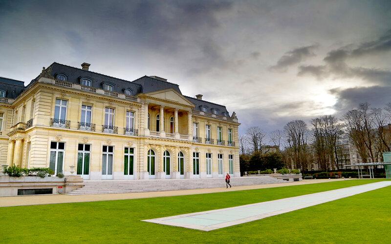 Seseorang tengah berjalan di depan Chateaux de la Muette, kantor pusat OECD, di Paris, Prancis - OECD
