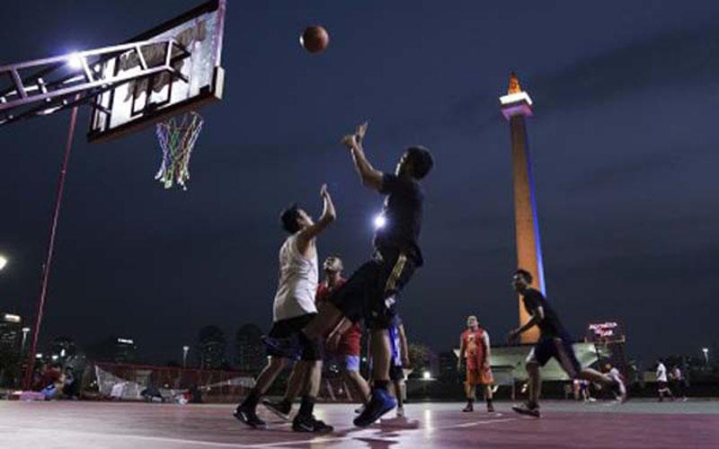 Ilustrasi sejumlah anak muda bermain basket di lapangan dekat Monumen Nasional (Monas) di Jakarta./Antara - Wahyu Putro
