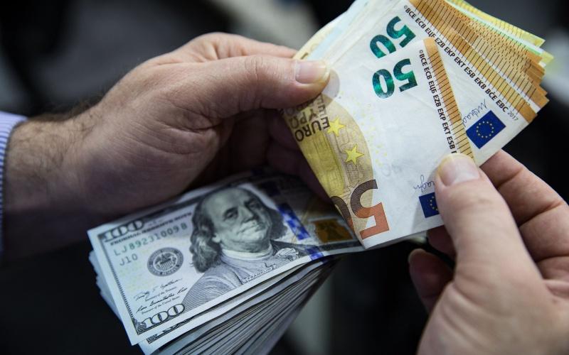 Seorang pria menghitung lembaran uang euro dan dolar AS. - Bloomberg/Kerem Uzel