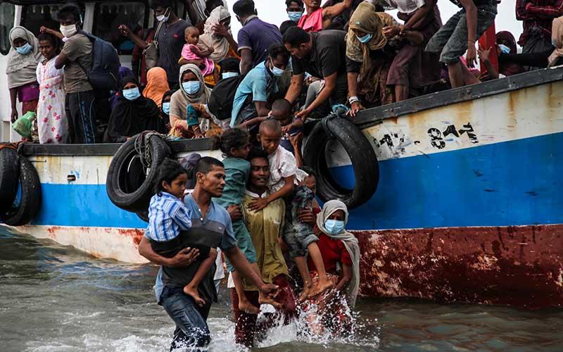 Warga mengevakuasi pengungsi etnis Rohingya dari kapal di pesisir pantai Lancok, Aceh Utara, Aceh, pada Kamis (25/6/2020). - Antara/Rahmad