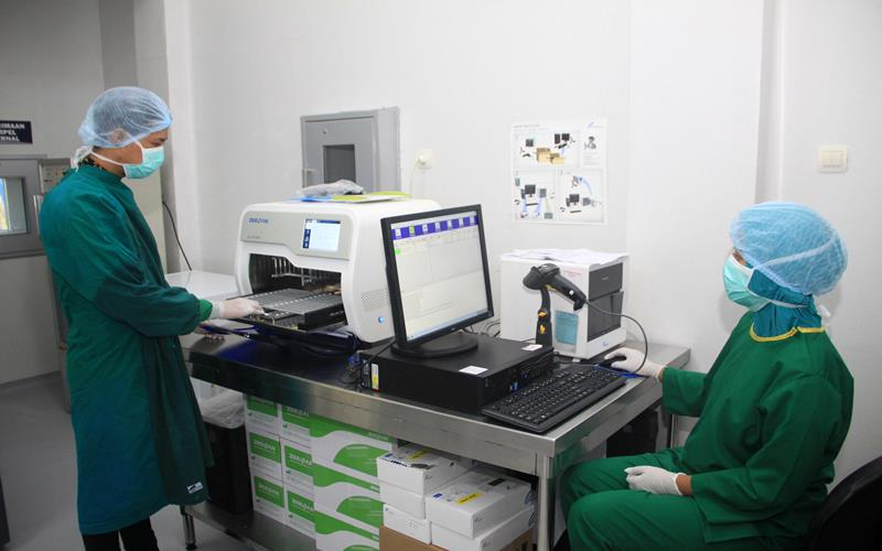 Dokter patologi klinik menunjukkan cara kerja alat Polymerase Chain Reaction (PCR) di Ruang Ektraksi DNA dan RNA Laboratorium Mikrobiologi RSUD Sidoarjo, Jawa Timur, Sabtu (20/6/2020). Pengoperasian alat PCR yang dapat memeriksa 1.000 sampel tersebut, diharapkan bisa mempercepat waktu untuk mengetahui hasil pemeriksaan pasien yang diduga terinfeksi virus corona atau Covid-19 di Sidoarjo. ANTARA FOTO - Umarul Faruq