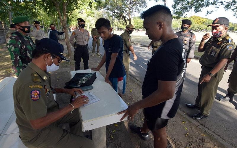 Satpol PP Provinsi Bali menindak warga yang tidak memakai masker saat beraktivitas di Lapangan Puputan Margarana, Renon, Denpasar, Bali, Senin (7/9/2020). Pemprov Bali mulai secara bertahap menerapkan sanksi denda sebesar Rp100 ribu bagi warga yang melanggar protokol kesehatan Covid-19 khususnya penggunaan masker untuk meningkatkan kedisiplinan dalam upaya menekan jumlah kasus Covid-19 di Bali yang terus bertambah. - Antara/Nyoman Hendra Wibowo