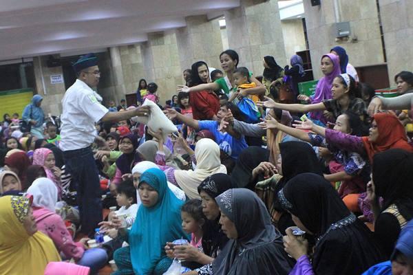 Petugas membagikan beras zakat di Masjid Istiqlal, Jakarta, Kamis (16/7). Panitia Zakat Masjid Istiqlal membagikan 15 ton beras bagi 3000 jamaah dengan bobot 5 kilogram per karungnya. - Antara