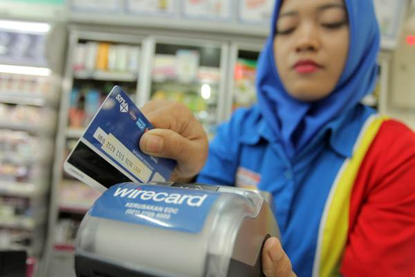 Karyawan minimarket menggesekan kartu debit di mesin Electronic Data Capture (EDC), di Jakarta. - ANTARA/Muhammad Adimaja