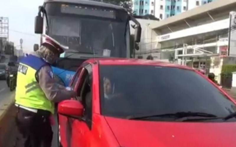 Polisi lalu lintas menilang pengendara mobil yang melintas di jalur TransJakarta Jalan Raya Jatinegara Barat, Jakarta Timur, Jumat (24/7/2020). - ANTARA/Andi Firdaus