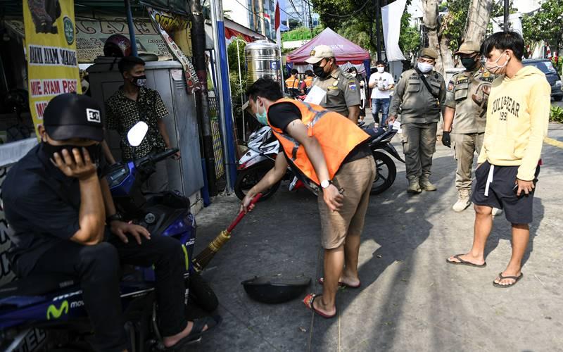 Petugas Satpol PP mengawasi pelanggar aturan pembatasan sosial berskala besar (PSBB) melaksanakan sanksi kerja sosial dengan menyapu sampah di kawasan Sabang, Jakarta, Senin (10/8/2020). ANTARA FOTO - M Risyal Hidayat