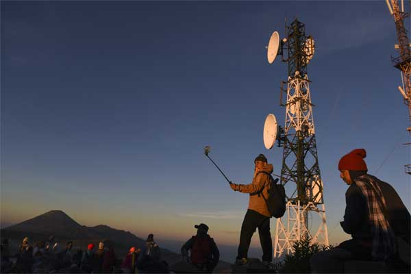 Wisatawan menikmati pemandangan Gunung Bromo dengan latar belakang Base Transceiver Station (BTS) Telkomsel di penanjakan satu Probolinggo, Jawa Timur, Jumat (19/5). - Antara/Zabur Karuru