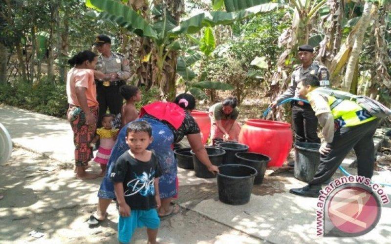 Anggota kepolisian membantu penyaluran bantuan air bersih kepada warga desa di Pulau Lombok, NTB, yang terdampak kekeringan. ANTARA/HO - Polres Lobar