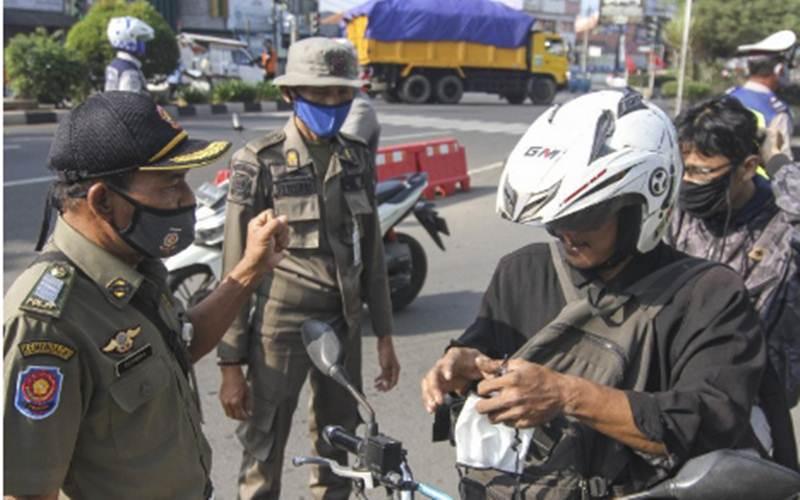 Petugas menegur pengendara yang tidak memakai masker dalam sosialisasi gerakan bermasker di Jalan Margonda Raya, Depok, Jawa Barat, Senin (20/7/2020). - Antara/Asprilla Dwi Adha
