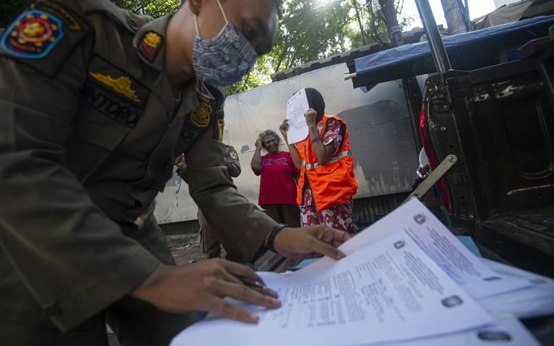 Petugas Satpol PP mendata warga yang melanggar aturan protokol kesehatan COVID-19 selama masa Pembatasan Sosial Berskala Besar (PSBB) transisi di kawasan Juanda, Jakarta, Jumat (21/8/2020). Pemerintah Provinsi DKI Jakarta mulai menerapkan Peraturan Gubernur Nomor 79 tahun 2020 yang berisi sanksi bagi setiap warga, pelaku usaha dan penanggung jawab fasilitas umum (fasum) yang berulang kali melanggar protokol kesehatan Covid-19 berupa sanksi kerja sosial membersihkan sarana fasum. - Antara
