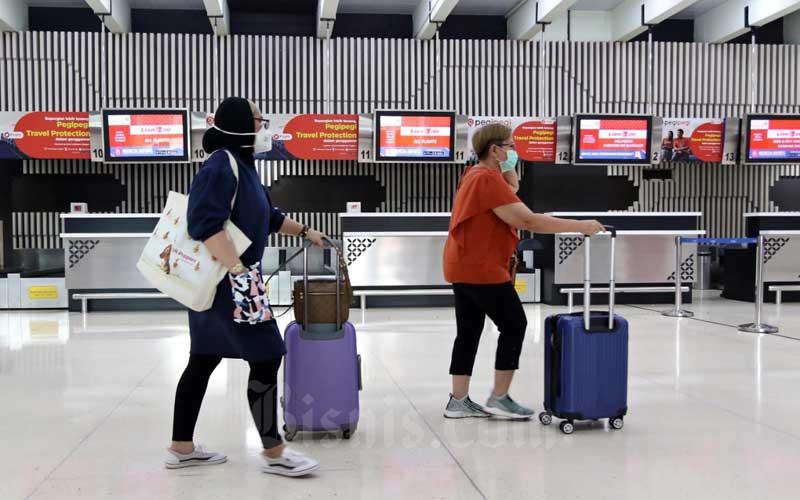 Sejumlah penumpang berada di konter check-in di Terminal IA Bandara Soekarno Hatta, Tangerang, Banten, Selasa (17/3/2020). Bisnis - Eusebio Chrysnamurti
