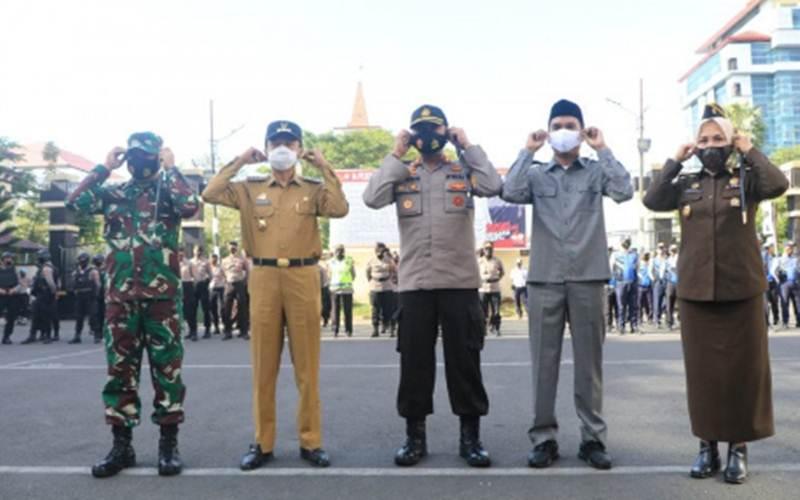 Penjabat Wali Kota Makassar Rudy Djamaluddin (dua dari kiri), bersama unsur Forum Komunikasi Pimpinan Daerah Makassar saat apel gelar pasukan operasi yustisi penegakan protokol Covid-19 di Makassar, Senin. - Antara/HO
