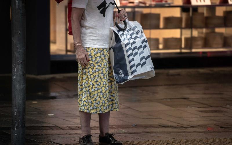 Warga Hong Kong membawa tas belanja dari sebuah department store ternama di Hong Kong, China, Sabtu (30/5/2020). - Bloomberg/Ivan Abreu