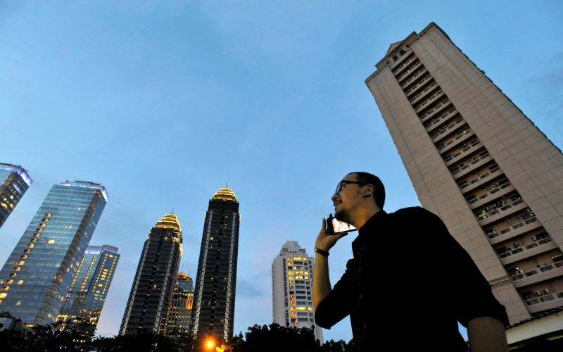 Seorang pria menelepon dengan latar belakang gedung perkantoran di kawasan bisnis terpadu Sudirman Central Business District (SCBD), Jakarta./Antara - Andika Wahyu