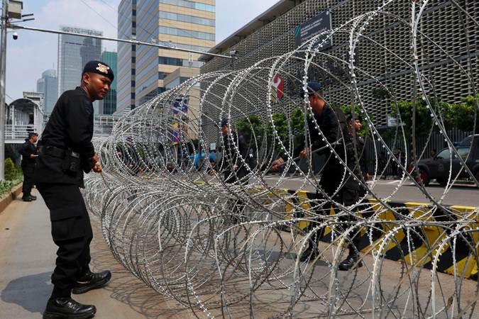 Petugas kepolisian memasang barikade kawat berduri di depan kantor Bawaslu, di Jakarta, Selasa (21/5/2019). - Bisnis/Abdullah Azzam