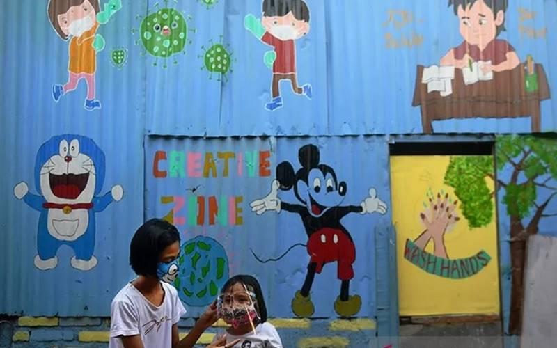 Dua orang anak menggunakan masker pelindung wajah saat bermain di depan mural bertema Covid-19 di Jakarta, Senin (27/7/2020). - Antara\n\n