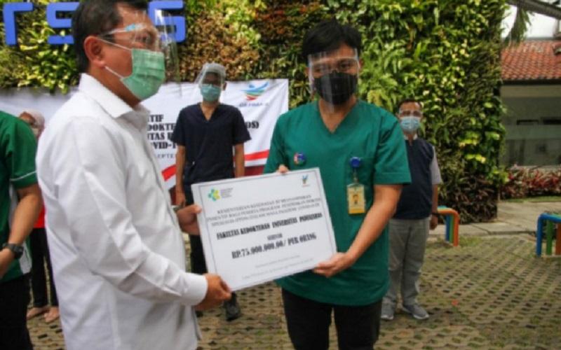 Menteri Kesehatan Terawan Agus Putranto (kiri) menyerahkan insentif bagi peserta PPDS FK Unpad sebesar Rp75 juta - Antara