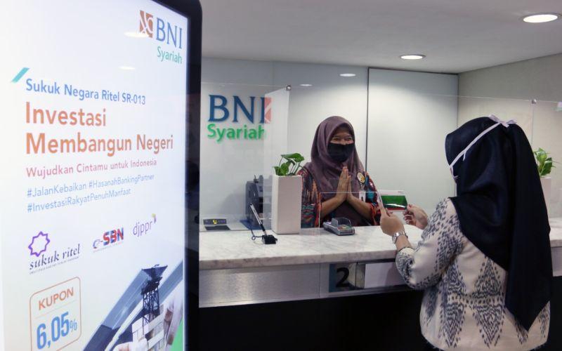 Nasabah sedang melakukan transaksi pembelian Sukuk Ritel SR013 melalui kantor cabang BNI Syariah, Jumat (28/8). - bnisyariah\r\n