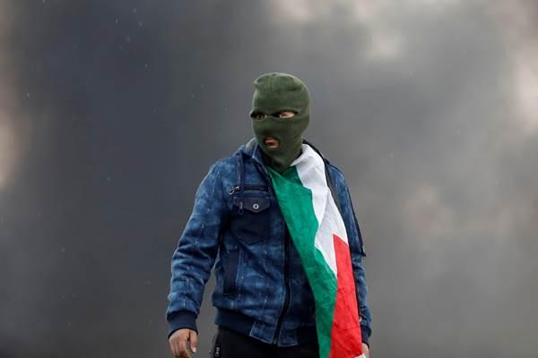 Seorang demonstran dari pihak Palestina saat bentrok dengan pasukan Israel di dekat Nablus, di Tepi Barat. - Reuters
