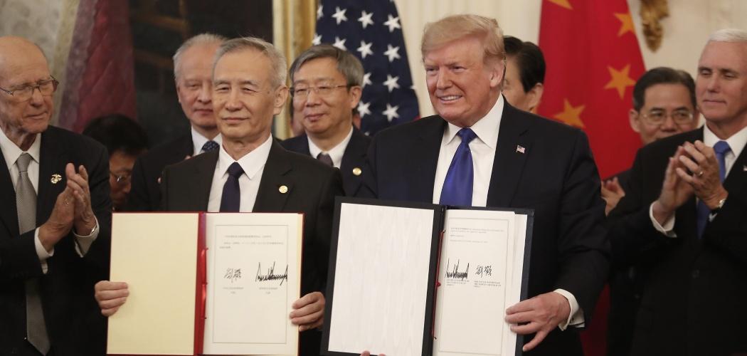 Wakil Perdana Menteri (PM) China Liu He (kiri) dan Presiden AS Donald Trump (kanan) menunjukkan kesepakatan fase pertama terkait penyelesaian sengketa dagang kedua negara di Gedung Putih, Washington DC, AS, Rabu (15/1/2020). - Bloomberg/Zach Gibson