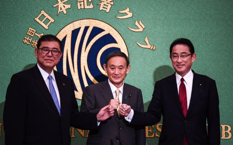Yoshihide Suga (tengah) berforo bersama Shigeru Ishiba (kiri) dan Fumio Kishida (kanan). Suga memenangkan 377 dari 535 suara dalam pemilihan ketua Partai Demokratik Liberal, menggantikan Shinzo Abe. - Bloomberg