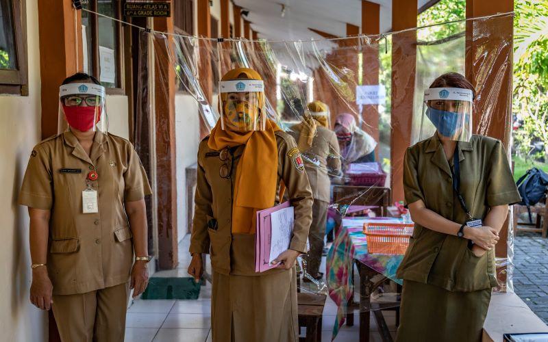 Sejumlah panitia Penerimaan Peserta Didik Baru (PPDB) mengenakan masker dan pelindung wajah saat pelaksanaan pendaftaran PPDB Tahun Pelajaran 2020/2021 di SDN Karangayu 02, Kelurahan Karangayu, Kota Semarang, Jawa Tengah, Senin (15/6/2020). ANTARA FOTO - Aji Styawan